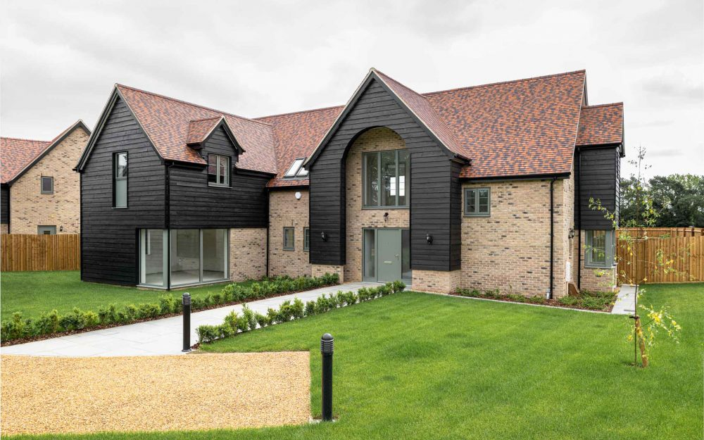 New-build home with black cladding and red roof tiles