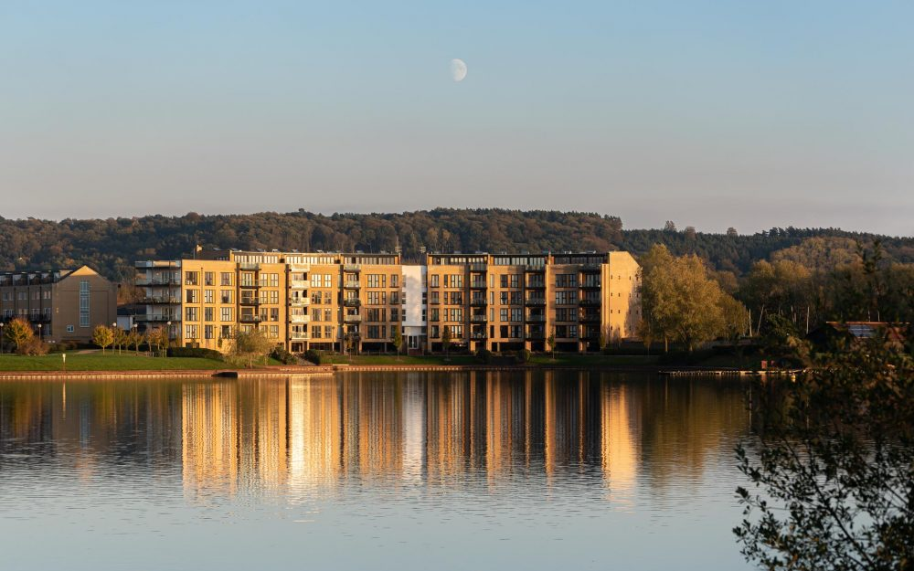 Lakeside apartments at sunset reflecting onto water