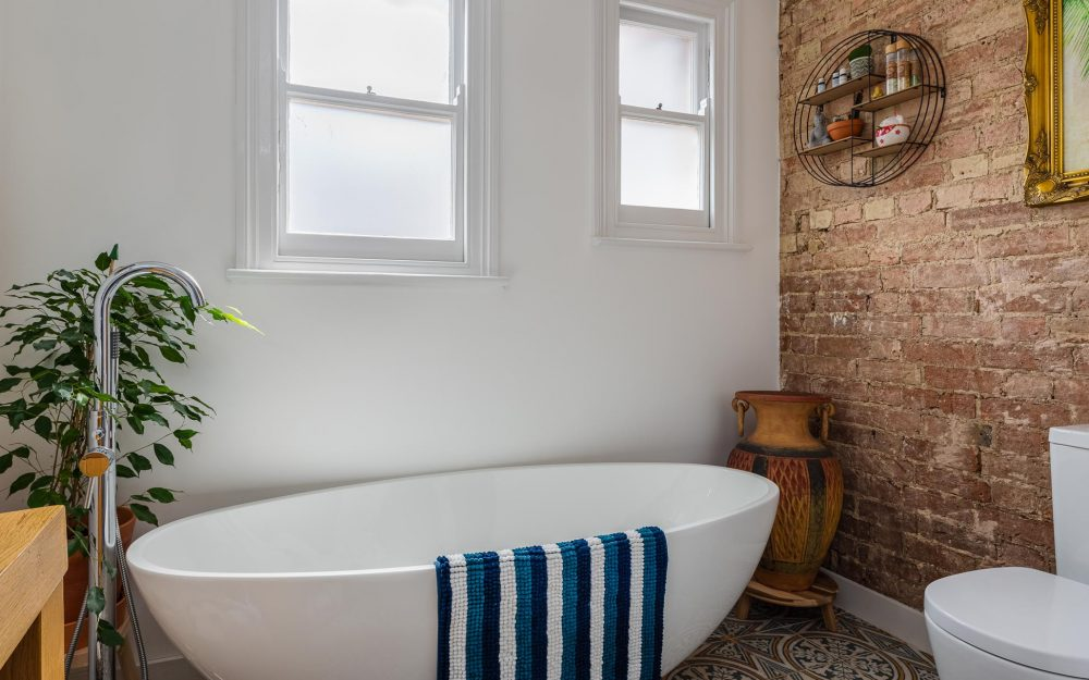 Contemporary white bath tub next to bare brick wall