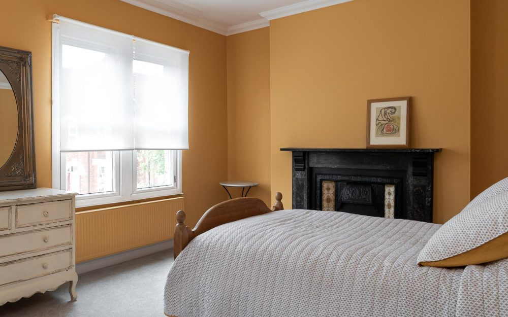 Bedroom painted with mustard colour walls